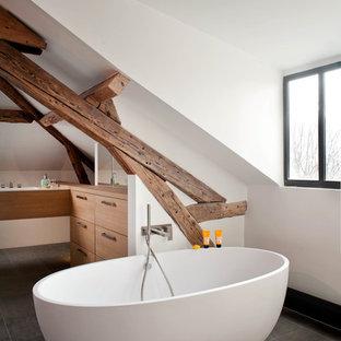 Réalisation d'une salle de bain design avec un placard à porte plane, des portes de placard en bois brun, une baignoire indépendante et un mur blanc.