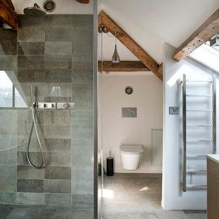Idée de décoration pour une grand salle d'eau design avec un WC suspendu, un carrelage gris, des carreaux de béton, un mur blanc, béton au sol et une douche d'angle.