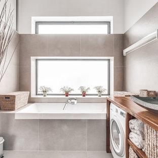 Foto de cuarto de baño principal, contemporáneo, pequeño, con armarios abiertos, bañera esquinera, ducha a ras de suelo, baldosas y/o azulejos grises, baldosas y/o azulejos de porcelana, paredes beige, suelo de baldosas de porcelana, lavabo encastrado, encimera de madera, suelo gris y encimeras marrones