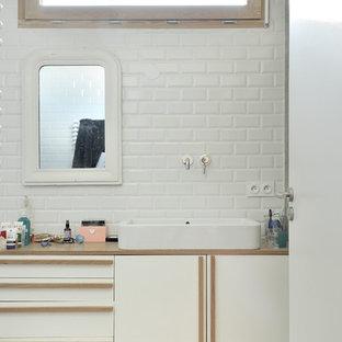 Exemple d'une salle de bain principale scandinave de taille moyenne avec des portes de placard blanches, un mur blanc, un sol en carrelage de céramique, une vasque, un plan de toilette en bois, un carrelage blanc, un carrelage métro et un plan de toilette marron.