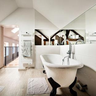 Cette image montre une grand salle de bain principale design avec une baignoire sur pieds, un carrelage blanc, un mur blanc et un sol en bois clair.