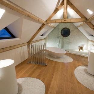 Inspiration pour une grand salle de bain principale design avec un sol en galet, une baignoire indépendante, une douche ouverte, un mur blanc et aucune cabine.