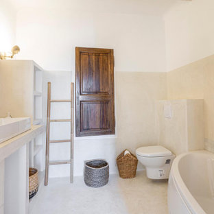 This is an example of a medium sized coastal bathroom in Other with open cabinets, an alcove bath, a wall mounted toilet, beige walls, terracotta flooring, a built-in sink, beige floors and beige worktops.