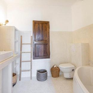 Bild på ett mellanstort maritimt beige beige badrum, med öppna hyllor, ett badkar i en alkov, en vägghängd toalettstol, beige väggar, klinkergolv i terrakotta, ett nedsänkt handfat och beiget golv
