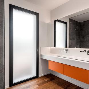 Inspiration pour une salle de bain design avec un placard à porte plane, des portes de placard oranges, un carrelage gris, un mur blanc, un sol en bois brun, une grande vasque et un plan de toilette blanc.