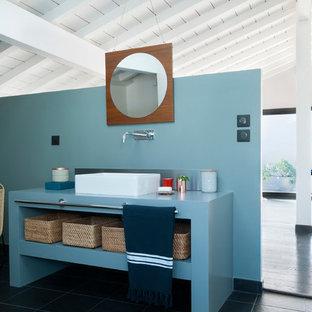 Aménagement d'une salle de bain bord de mer avec un placard sans porte, des portes de placard bleues, un mur bleu, une vasque, un sol noir et un plan de toilette bleu.