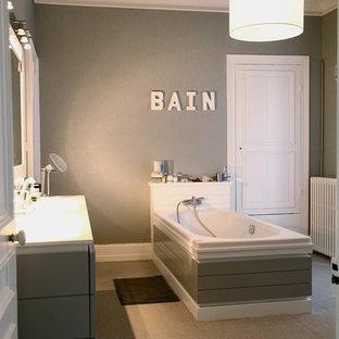 Idée de décoration pour une grande salle de bain principale design avec des portes de placard grises, une baignoire posée et un mur gris.