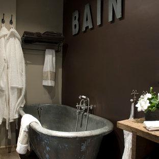 Cette photo montre une salle de bain principale industrielle de taille moyenne avec une baignoire sur pieds, un mur marron, un placard sans porte et un sol en bois brun.