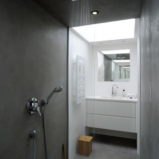 Scandinavian 3/4 bathroom in Lyon with flat-panel cabinets, white cabinets, a curbless shower, white walls, concrete floors and an integrated sink.