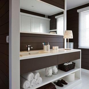 Cette image montre une salle de bain design de taille moyenne avec un lavabo posé, un placard à porte plane, des portes de placard en bois sombre et un mur marron.