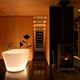 Réalisation d'une grande salle de bain principale design avec des portes de placard en bois brun, une baignoire indépendante et un sol noir.