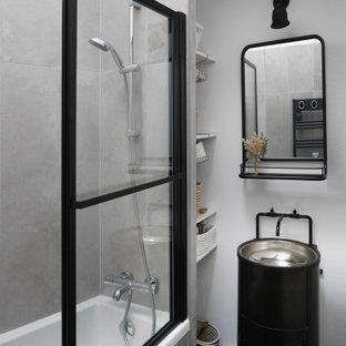 Foto di una piccola stanza da bagno padronale industriale con nessun'anta, ante bianche, vasca da incasso, piastrelle grigie, piastrelle in ceramica, pareti bianche, pavimento in cemento, lavabo da incasso, top in acciaio inossidabile, pavimento grigio e top nero