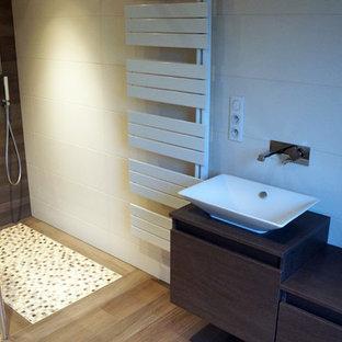 Diseño de cuarto de baño principal, contemporáneo, grande, con puertas de armario de madera en tonos medios, ducha a ras de suelo, baldosas y/o azulejos beige, suelo de baldosas tipo guijarro, paredes beige, suelo de madera clara, lavabo sobreencimera y encimera de madera