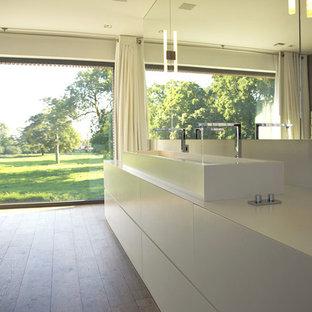 Réalisation d'une très grand salle de bain principale design avec des portes de placard blanches, un mur gris, un sol en bois brun et une grande vasque.