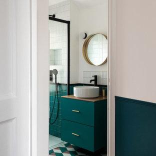 Inredning av ett modernt litet beige beige badrum med dusch, med släta luckor, blå skåp, en kantlös dusch, vit kakel, keramikplattor, vita väggar, cementgolv, ett fristående handfat, träbänkskiva, blått golv och dusch med skjutdörr