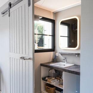 Idées déco pour une salle de bain contemporaine avec un placard sans porte, des portes de placard blanches, un mur gris, un sol en bois brun, un lavabo posé, un sol marron et un plan de toilette gris.