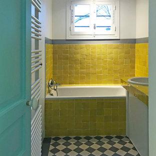 Kleines Stilmix Kinderbad mit Unterbauwanne, Duschnische, gelben Fliesen, Keramikfliesen, gelber Wandfarbe, Zementfliesen, gefliestem Waschtisch, grauem Boden und gelber Waschtischplatte in Paris
