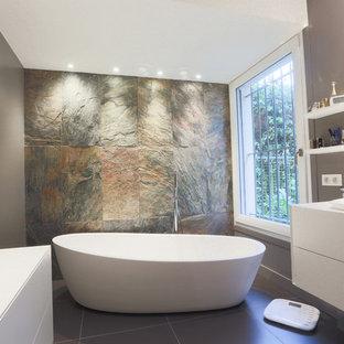 Réalisation d'une salle de bain principale design de taille moyenne avec un placard à porte plane, des portes de placard blanches, une baignoire indépendante, un mur gris, un carrelage de pierre et un lavabo encastré.