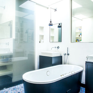 Example of a mid-sized eclectic master multicolored tile and blue tile ceramic floor freestanding bathtub design in Paris with black cabinets, white walls and a vessel sink