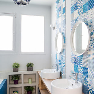 Tuscan blue tile, white tile and cement tile concrete floor and gray floor bathroom photo in Toulouse with open cabinets, white walls, a vessel sink, wood countertops and beige countertops