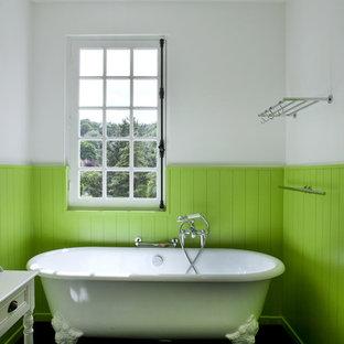 Réalisation d'une salle de bain champêtre avec une baignoire sur pieds et un mur vert.