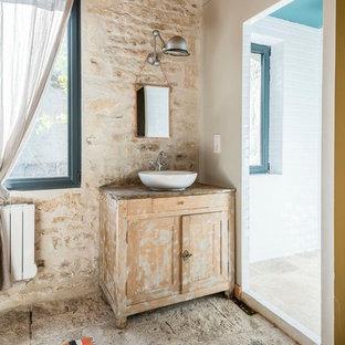 Réalisation d'une salle de bain méditerranéenne avec un placard en trompe-l'oeil, des portes de placard en bois clair, un carrelage beige, un carrelage de pierre, un mur blanc, une vasque, un plan de toilette en bois, un sol gris et un plan de toilette marron.