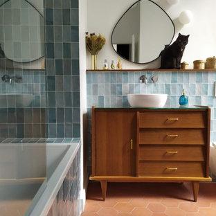 Cette photo montre une salle d'eau tendance de taille moyenne avec un placard en trompe-l'oeil, des portes de placard en bois brun, une baignoire en alcôve, un combiné douche/baignoire, un carrelage bleu, un mur blanc, un sol en carreau de terre cuite, une vasque, un plan de toilette en verre, un sol orange, aucune cabine, un plan de toilette bleu, meuble simple vasque et meuble-lavabo sur pied.