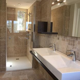 Foto di una stanza da bagno con doccia mediterranea con doccia a filo pavimento, piastrelle in travertino, pavimento in travertino, lavabo rettangolare, top in legno e porta doccia a battente