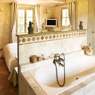 Photo of a medium sized mediterranean ensuite bathroom in Marseille with a submerged bath, beige tiles and terracotta flooring.