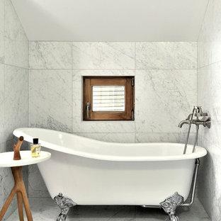 Inspiration pour une salle de bain traditionnelle avec une baignoire sur pieds et un sol gris.