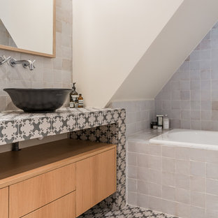 Photo of a mediterranean bathroom in Paris with flat-panel cabinets, medium wood cabinets, a built-in bath, white tiles, white walls, a vessel sink, tiled worktops, multi-coloured floors and multi-coloured worktops.