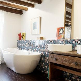 Новые идеи обустройства дома: большая главная ванная комната в стиле кантри с открытыми фасадами, светлыми деревянными фасадами, отдельно стоящей ванной, душем без бортиков, инсталляцией, синей плиткой, керамической плиткой, белыми стенами, полом из бамбука, накладной раковиной, столешницей из дерева, коричневым полом, открытым душем и коричневой столешницей