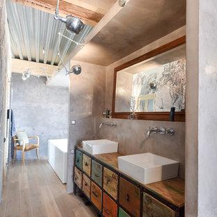 Esempio di una grande stanza da bagno padronale bohémian con lavabo a bacinella, consolle stile comò, ante con finitura invecchiata, top in legno, pareti grigie e vasca freestanding