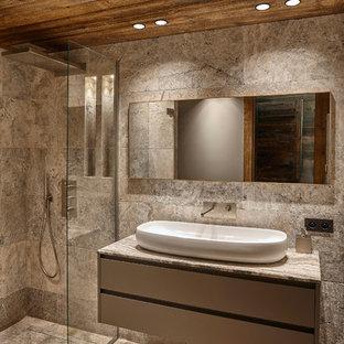 Foto de cuarto de baño con ducha, rústico, de tamaño medio, con puertas de armario grises, ducha a ras de suelo, baldosas y/o azulejos grises, losas de piedra, suelo de travertino, lavabo encastrado, encimera de piedra caliza, paredes marrones y ducha abierta