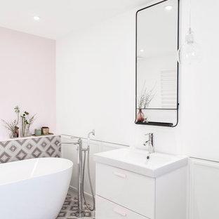 Réalisation d'une salle de bain design avec un placard à porte plane, des portes de placard blanches, une baignoire indépendante, un carrelage multicolore, un mur rose et un sol multicolore.