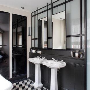 Cette image montre une douche en alcôve design de taille moyenne avec un placard à porte affleurante, des portes de placard en bois sombre, une baignoire sur pieds, un WC à poser, un carrelage noir et blanc, des carreaux de béton, un mur gris, un sol en carrelage de céramique et un lavabo de ferme.