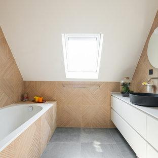 Cette image montre une salle d'eau design avec un placard à porte plane, des portes de placard blanches, une baignoire posée, une vasque, un sol gris et un plan de toilette blanc.