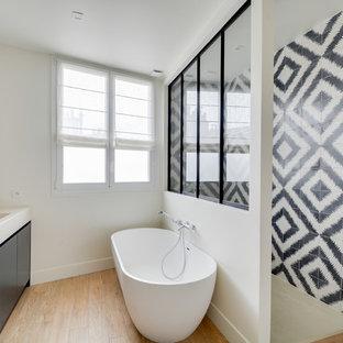 Idées déco pour une salle de bain contemporaine avec un placard à porte plane, des portes de placard noires, une baignoire indépendante, un carrelage noir et blanc, un carrelage multicolore, un mur blanc, un sol en bois clair, un lavabo intégré et aucune cabine.