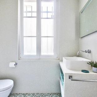 Réalisation d'une petite salle d'eau minimaliste avec des portes de placard blanches, une douche à l'italienne, un WC suspendu, un carrelage blanc, carrelage en mosaïque, un mur blanc, un sol en carreaux de ciment, un lavabo posé, un sol bleu et aucune cabine.