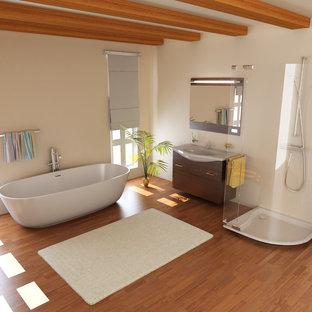 Réalisation d'une salle de bain principale design de taille moyenne avec un placard à porte affleurante, des portes de placard en bois sombre, une baignoire indépendante, une douche double, un WC séparé, un mur beige, sol en stratifié, un plan vasque, un sol marron, une cabine de douche à porte coulissante et un plan de toilette blanc.