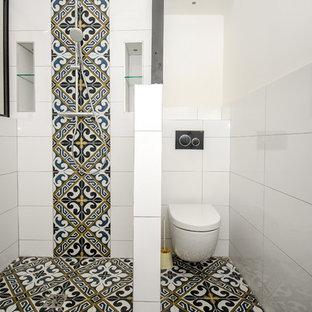 Imagen de cuarto de baño con ducha, urbano, grande, con ducha abierta, sanitario de pared, baldosas y/o azulejos blancos, baldosas y/o azulejos de terracota, paredes blancas, suelo de azulejos de cemento, lavabo tipo consola, encimera de acrílico, suelo negro y encimeras blancas