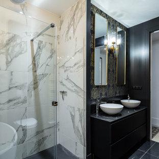 Idées déco pour une salle d'eau contemporaine de taille moyenne avec un placard à porte plane, des portes de placard noires, une douche d'angle, un carrelage noir, un mur noir, une vasque, un sol noir, une cabine de douche à porte coulissante et un plan de toilette noir.