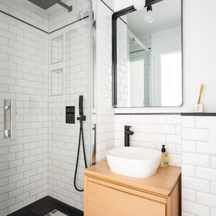 Inspiration for a small contemporary ensuite bathroom in London with flat-panel cabinets, light wood cabinets, a corner shower, white tiles, metro tiles, white walls, a vessel sink, wooden worktops, black floors, ceramic flooring, a hinged door and beige worktops.
