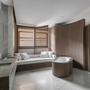 Cette photo montre une très grand salle de bain principale scandinave avec un lavabo intégré, un plan de toilette en marbre, une baignoire indépendante, un mur gris et un sol en marbre.