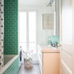 Idée de décoration pour une salle de bain design avec un placard à porte plane, des portes de placard blanches, une baignoire posée, un combiné douche/baignoire, un carrelage vert, un carrelage métro, un mur blanc, un plan vasque, un sol multicolore et une cabine de douche avec un rideau.