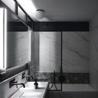 Idéer för ett mellanstort modernt vit en-suite badrum, med luckor med profilerade fronter, skåp i mörkt trä, ett undermonterat badkar, en toalettstol med separat cisternkåpa, svart och vit kakel, marmorkakel, gröna väggar, cementgolv, ett avlångt handfat, bänkskiva i akrylsten och grönt golv