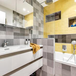 Foto di una piccola stanza da bagno padronale minimal con vasca sottopiano, vasca/doccia, piastrelle gialle, piastrelle in terracotta, pareti grigie, ante a filo, ante bianche, pavimento con piastrelle in ceramica e lavabo a consolle