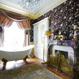 Exemple d'une grand salle de bain principale chic avec une baignoire sur pieds, un mur multicolore et un sol en bois brun.