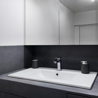Ejemplo de cuarto de baño principal, escandinavo, pequeño, con armarios con rebordes decorativos, puertas de armario grises, ducha empotrada, sanitario de pared, baldosas y/o azulejos grises, paredes grises, lavabo bajoencimera, encimera de cemento, suelo gris, ducha con puerta corredera y encimeras grises
