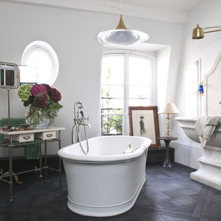 Inspiration for a large eclectic master dark wood floor freestanding bathtub remodel in Paris with a pedestal sink, furniture-like cabinets and white walls
